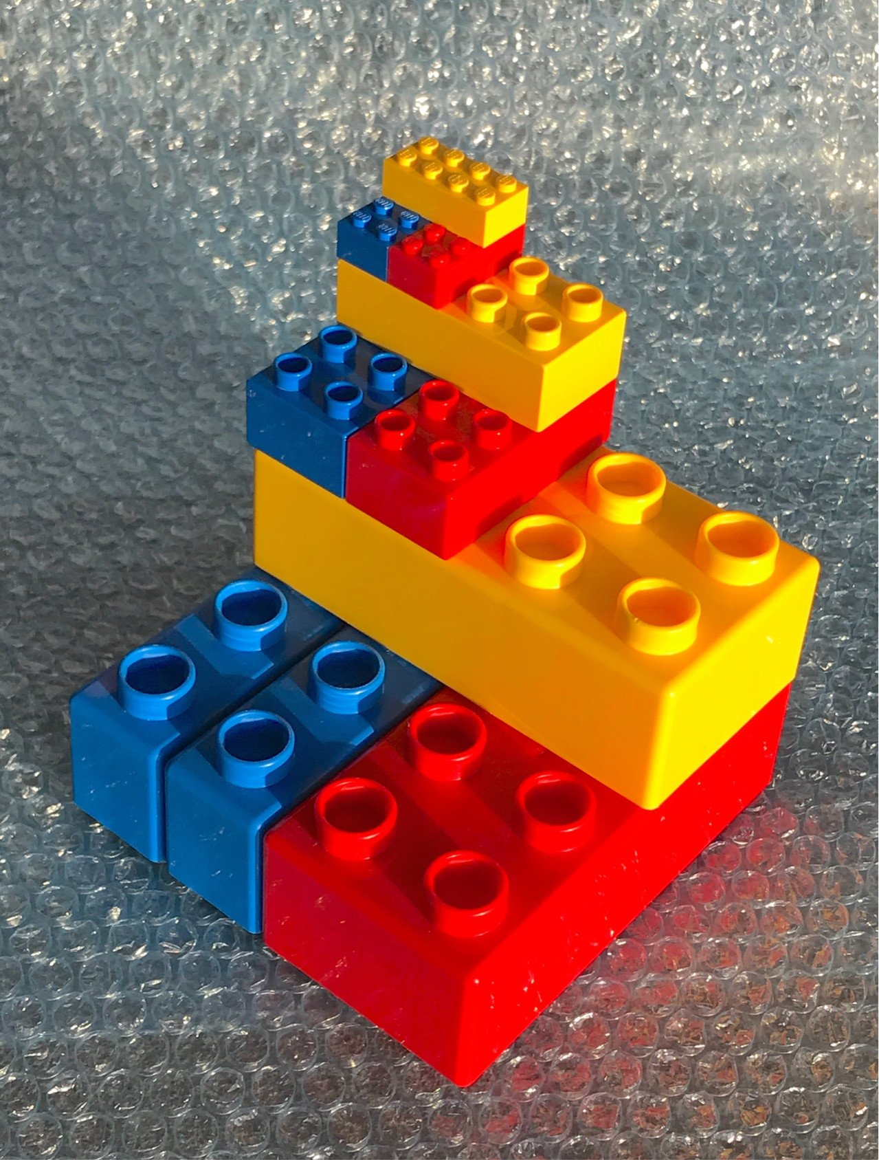 system, Duplo and Quatro bricks stacked